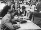 An officials meeting during the European Championships in Magdeburg in 1934. Of those people that can be identified, facing in the glasses is Harold Fern and standing behind with the cigarette, Ladislav Hauptmann. The person standing to the far left is likely to be Emile Drigny